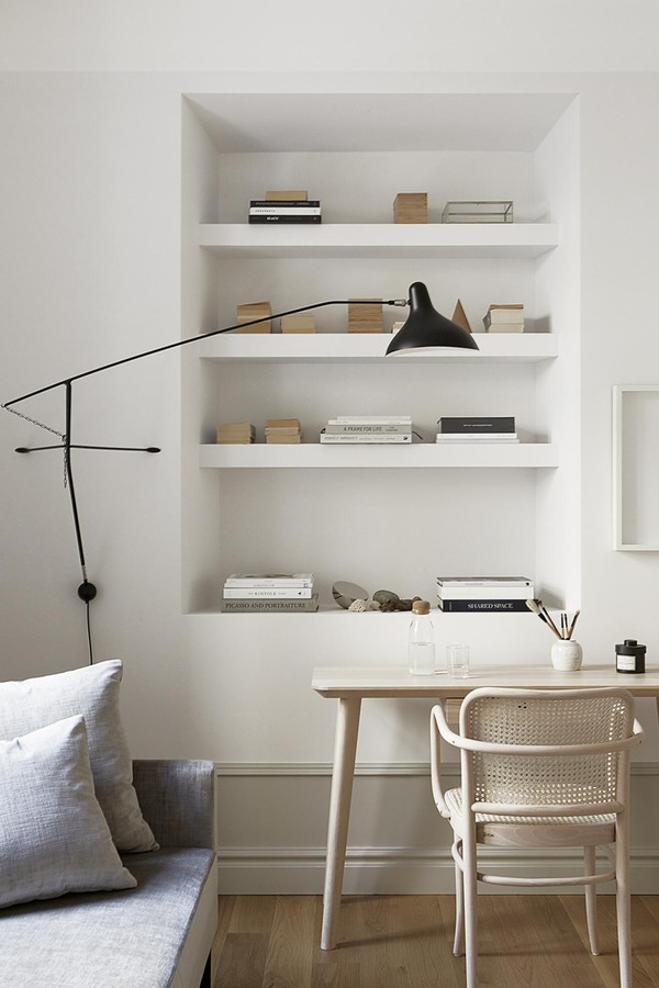 Scandinavian style desk, chair, modern black sconce, and plaster shelves in small Stockholm apartment