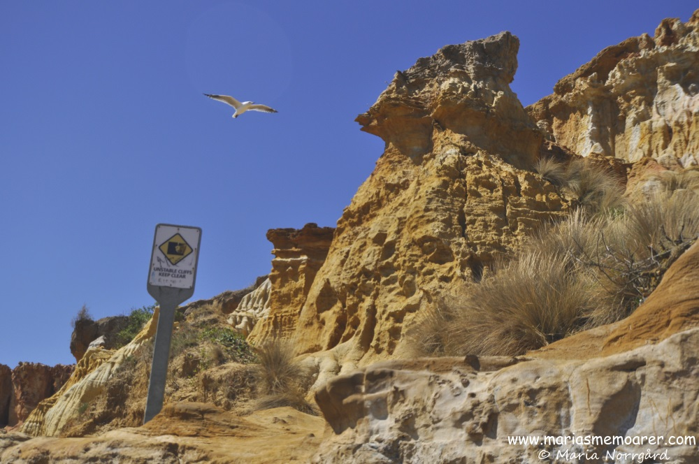 warning sign at Half Moon Bay red bluff cliffs due to instability