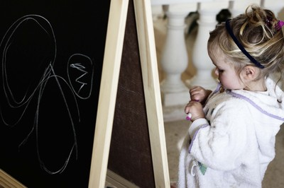 Young girl playing with black board, white board christmas present from Santa