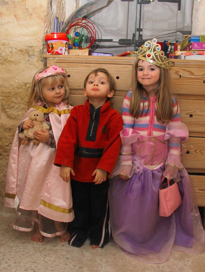 Three year old children, two girls and a boy, having fun playing dress up